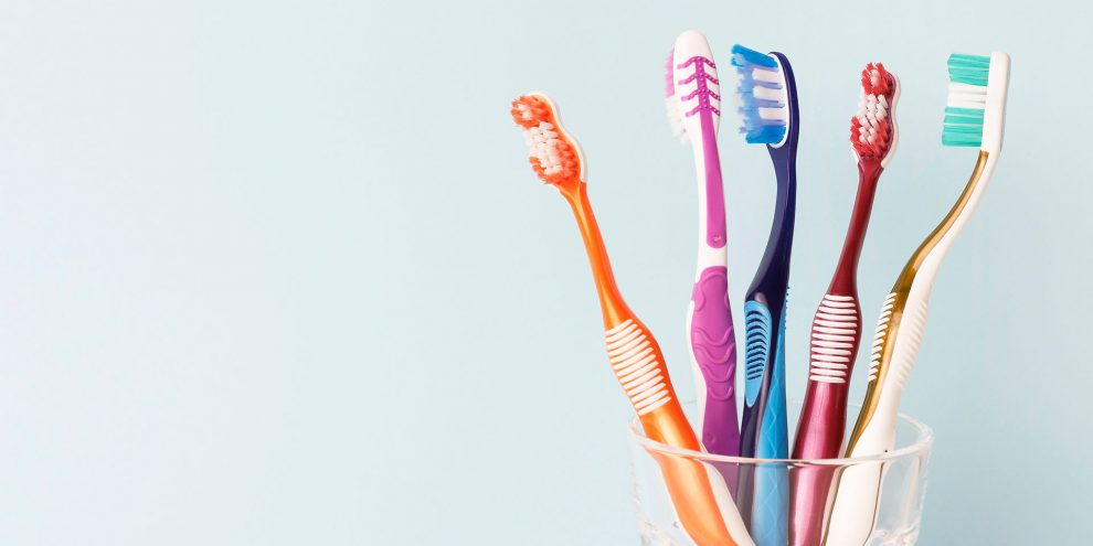 Five toothbrushes in a glass